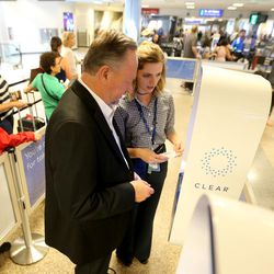 Paige Carter, CLEAR ambassador, helps Rex Falkenrath verify his identity for the first time with a new biometric, fee-based service that allows travelers to move past manual ID verification lines using fingerprints and iris scans, at the Salt Lake City International Airport in Salt Lake City on Wednesday, July 12, 2017.