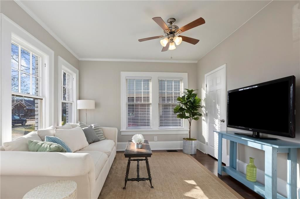 An off-white TV room with a brown ceiling fan overhead.