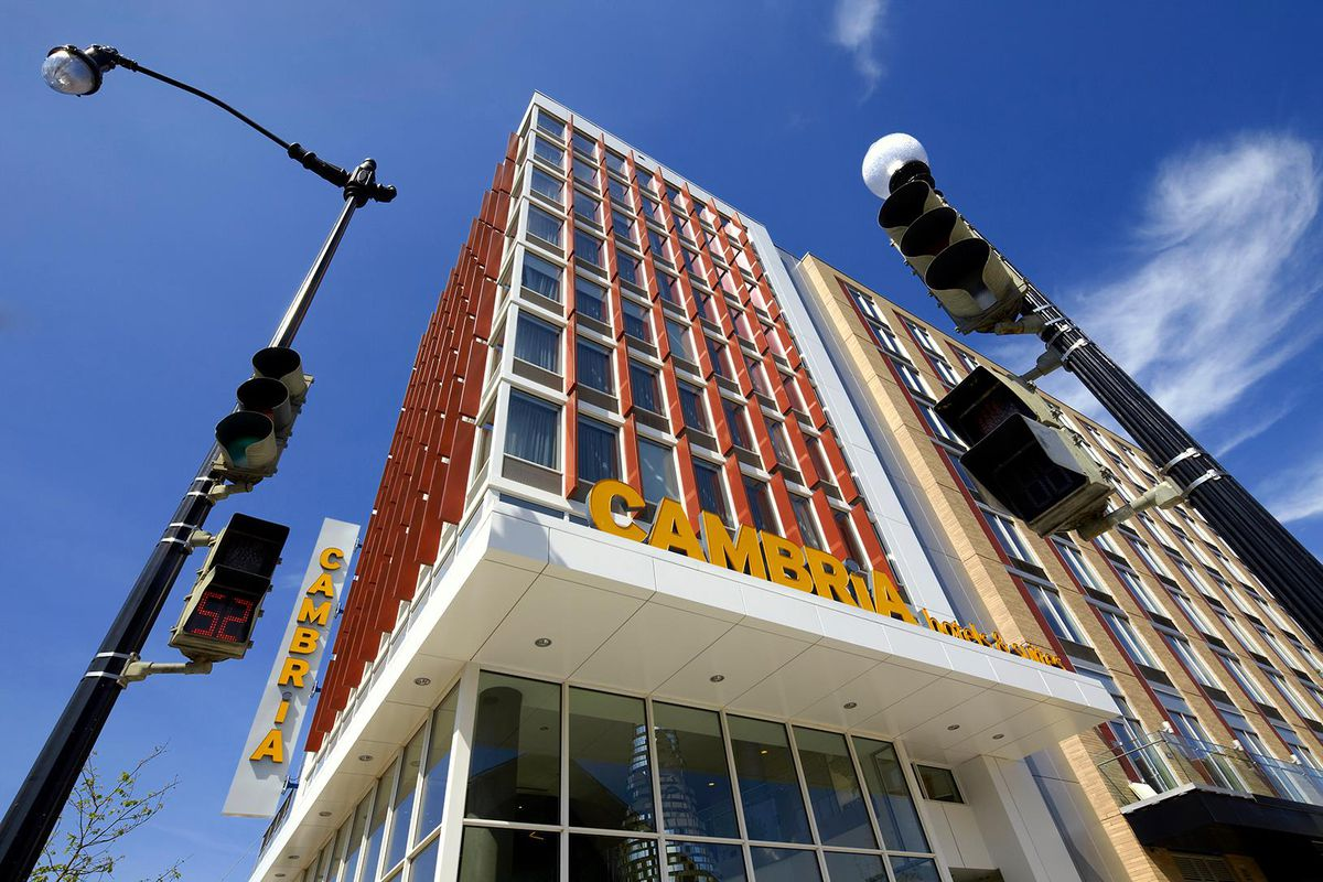 tall building shot from below, wintows, red girders, flat white mod awning with word Cambria on top.