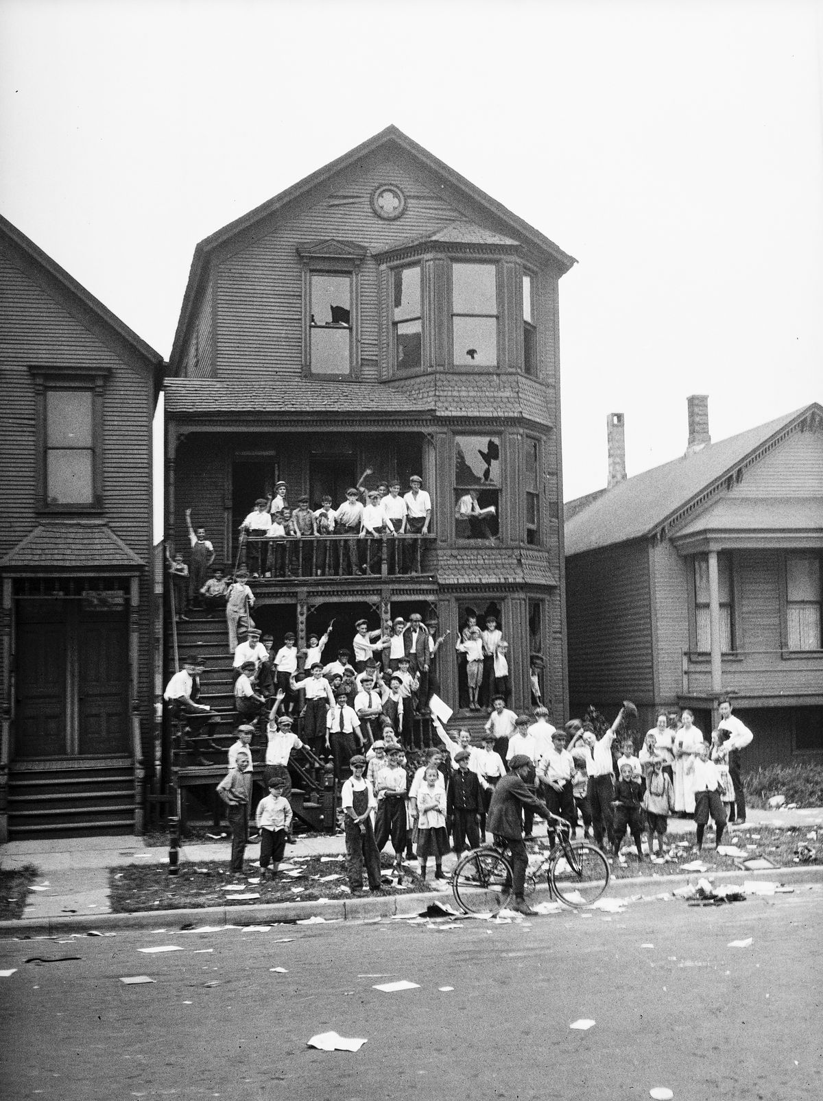 A crowd gathers at a house that has been vandalized and looted during the 1919 race riots in Chicago.