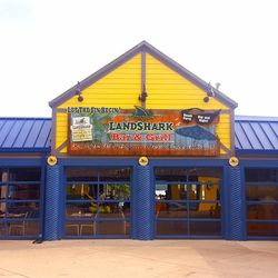 The side of the LandShark Bar & Grill faces a path leading to the rest of the park.