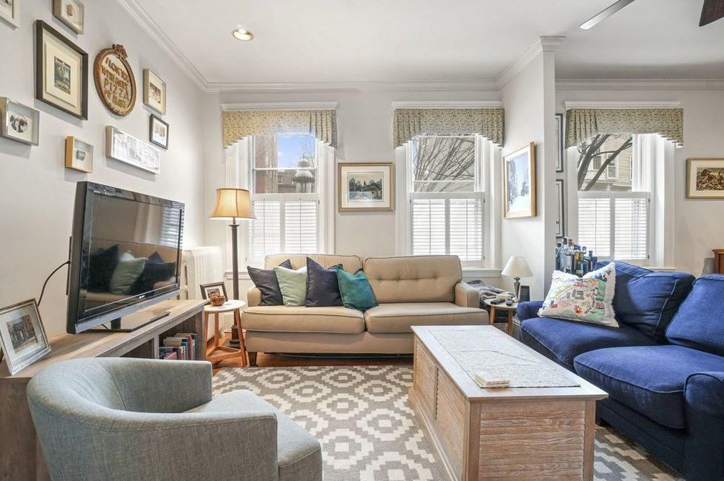 That living room, with two couches perpendicular to one another and facing a mounted TV.