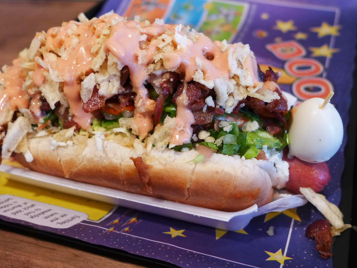 A giant heap of a hot dog smeared with sauces and a small boiled egg on the end.
