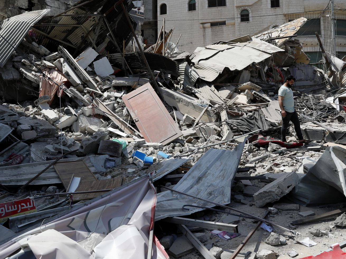 A man inspects the rubble of destroyed residential building which was hit by Israeli airstrikes, in Gaza City, Thursday, May 20, 2021.