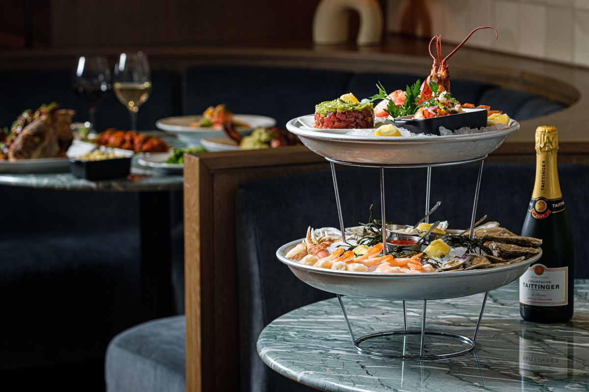 A two-tier seafood tower on round plates on a table.