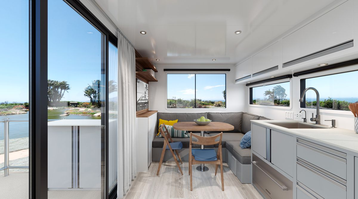 The interior of the trailer features an eight-foot sliding glass door on the left, a sink and kitchen area on the right, and a lounge area with cushions and two chairs in the rear.