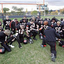 The Monticello Buckaroos kneel in prayer after beating Layton Christian 42-0 in 1A football action recently. The team has 36 players.
