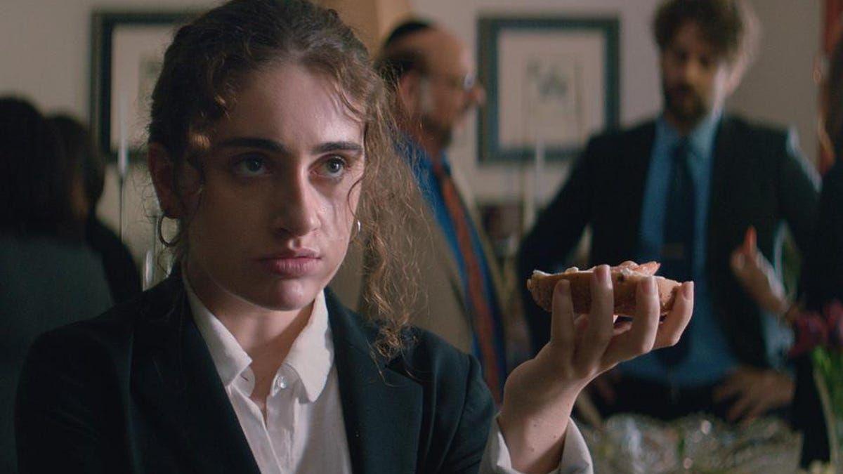 Rachel Sennott como Danielle sosteniendo un bagel con salmón ahumado en Shiva Baby