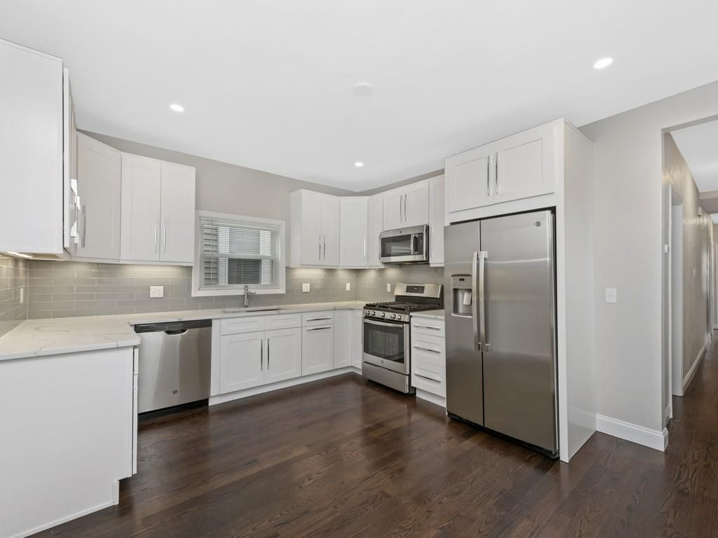 An open kitchen with a U-shaped counter and a large fridge.