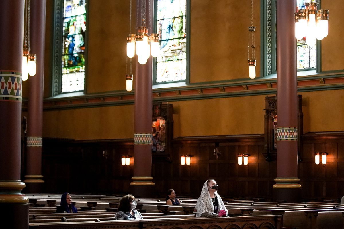 Ursula Quintana, center, and her mother, Joleen Rogers, second from left, sit together before Mass at the Cathedral of the Madeleine on Tuesday, May 12, 2020.