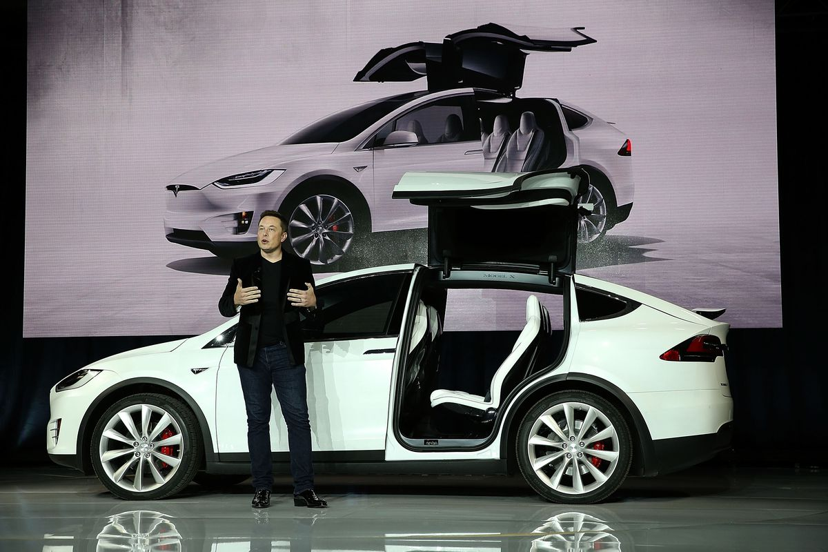 Elon Musk stands beside a Tesla Model X SUV with its gull-wing doors open.