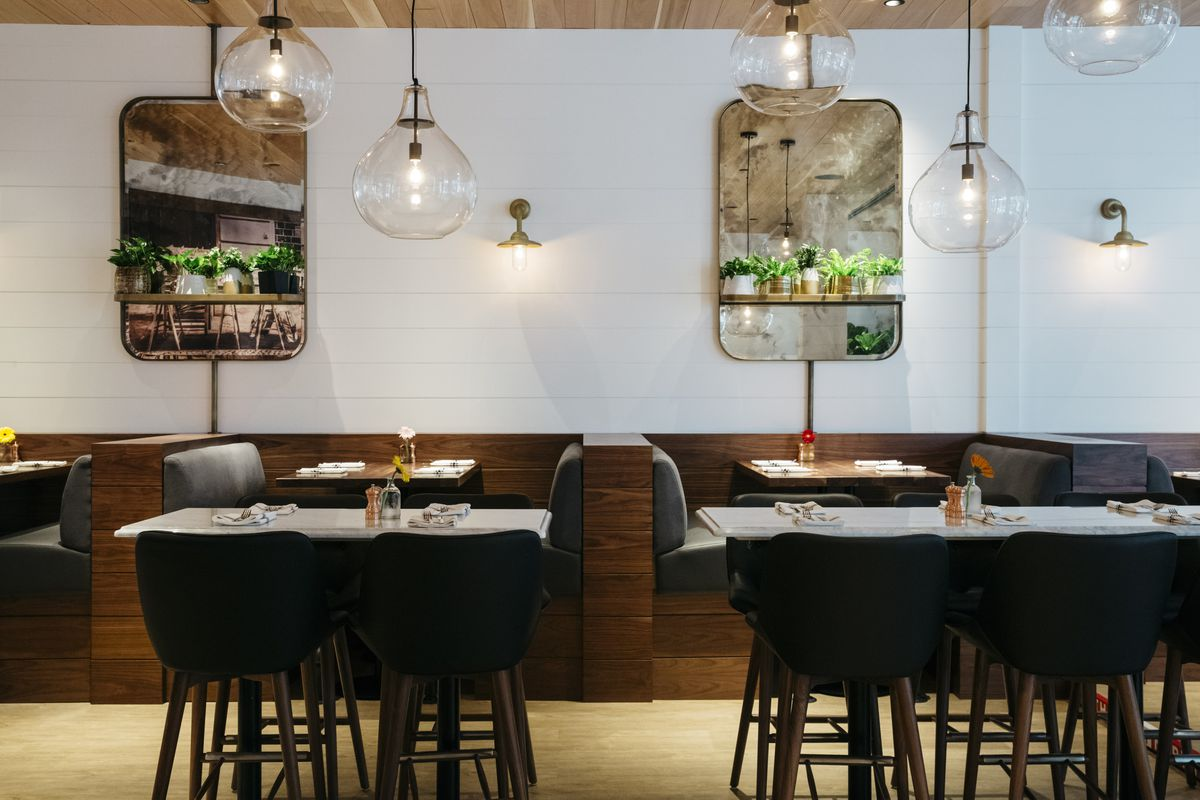 Vintage mirrors lined with greenery frame a wall of booths, below glowing glass orbs