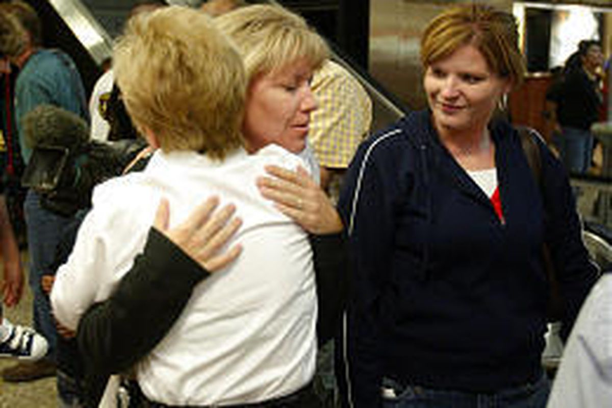 Lindsay Larsen, right, watches as Marcy Willits, center, gets a hug from Carol Groustra, bureau communications chief for the Utah Department of Public Safety, after landing at Salt Lake City International Friday.