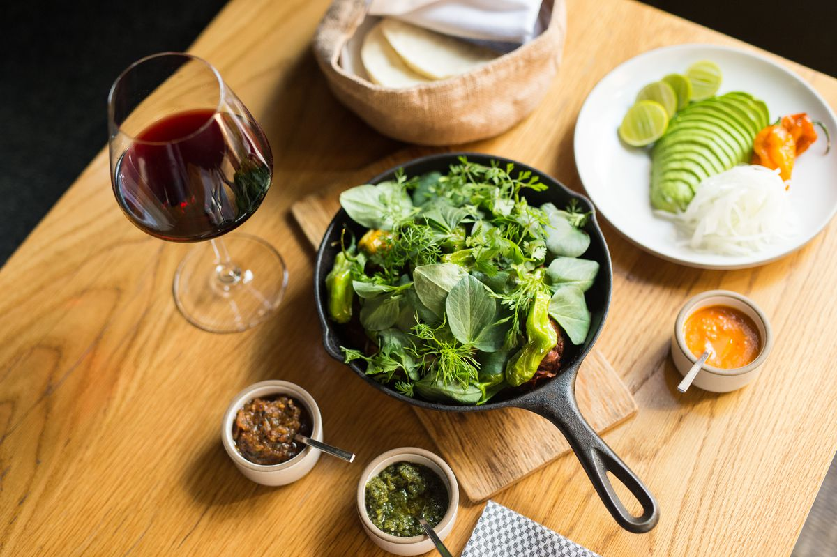 Cosme's lamb barbacoa in a cast iron pan, next to a glass of wine and a plate with avocado.