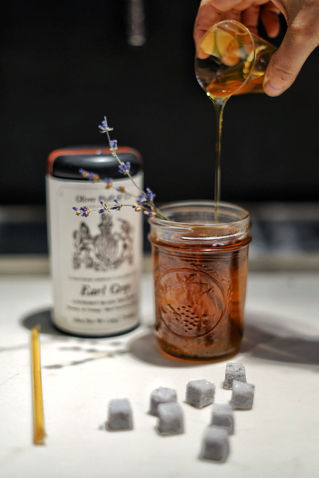 A mason jar filled with tea, garnished with a lavender sprig. Sugar cubes sit in front of it.