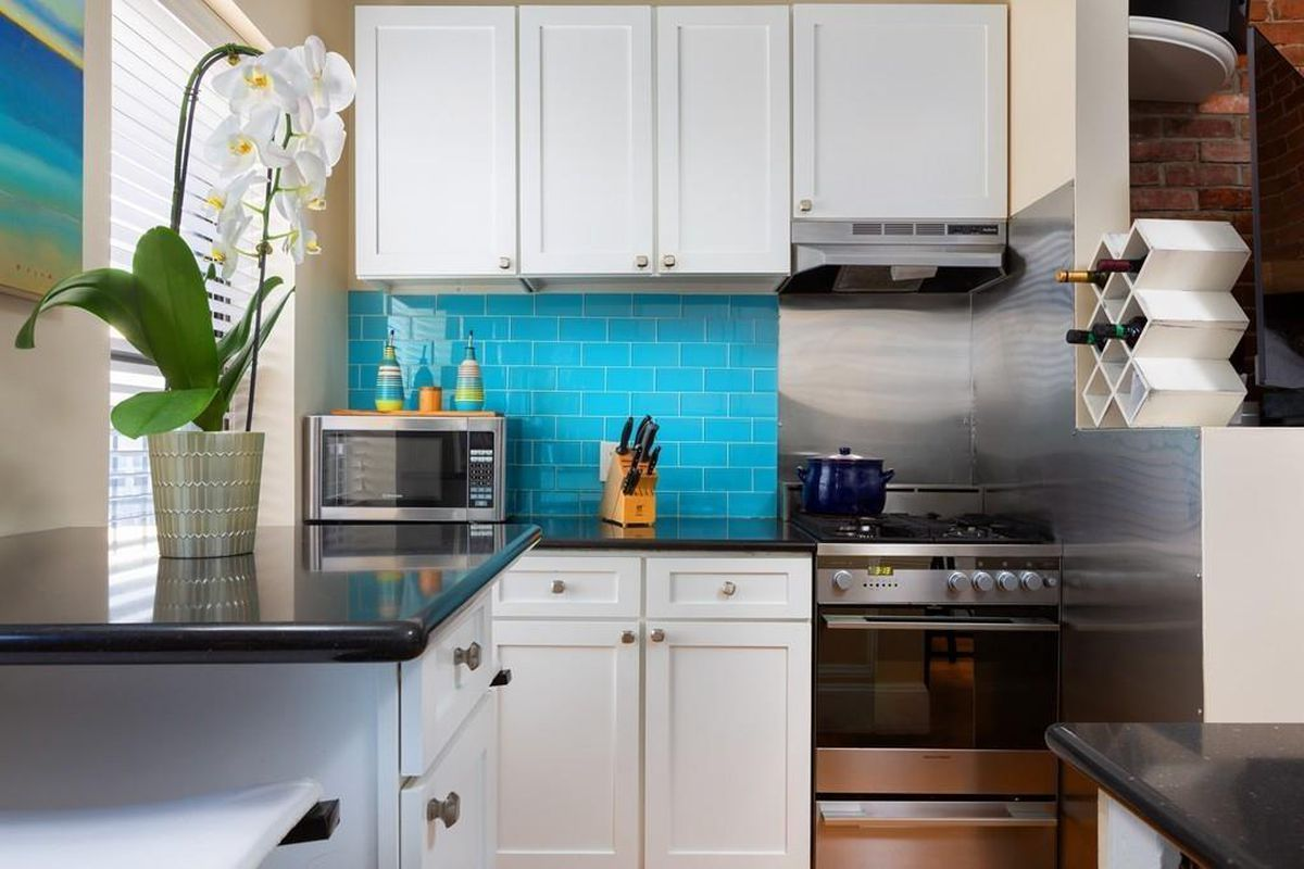 Cute, clean, small kitchen with a knife block on the counter prominently featured.