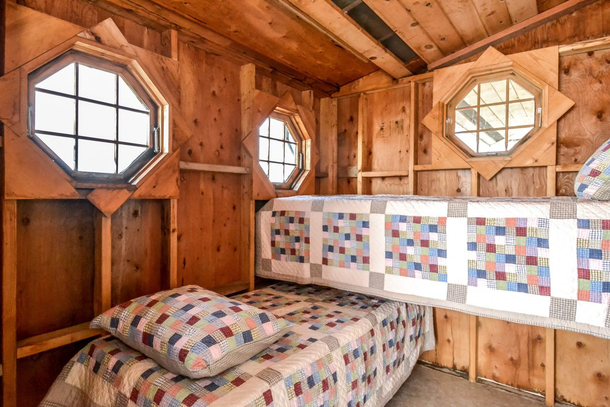 Two small twin beds sit cross style in a room with three porthole style windows.