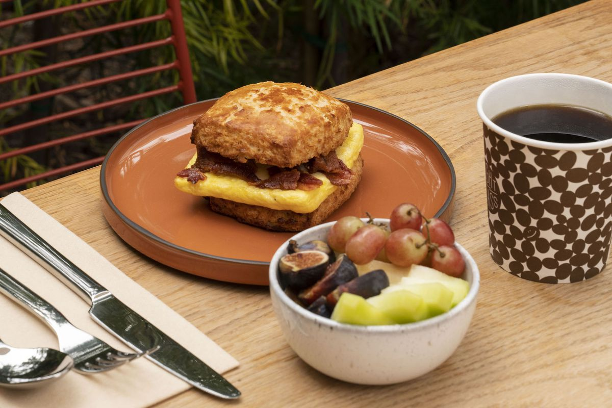 A side angle shot of a breakfast sandwich on a biscuit, sitting on a reddish plate on a wooden table.