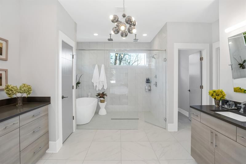 A large white master bathroom with a bubble fixture overhead and a white tub at center.