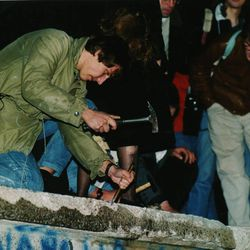 This Nov. 10, 1989 file photo shows a man atop the Berlin wall nearby the Brandenburger Tor (Brandenburg gate) in Germany as he chisels a piece of the wall that divided East and West Berlin. Monday, Nov. 9, 2009 marks the 20th anniversary of the fall of the Berlin Wall.