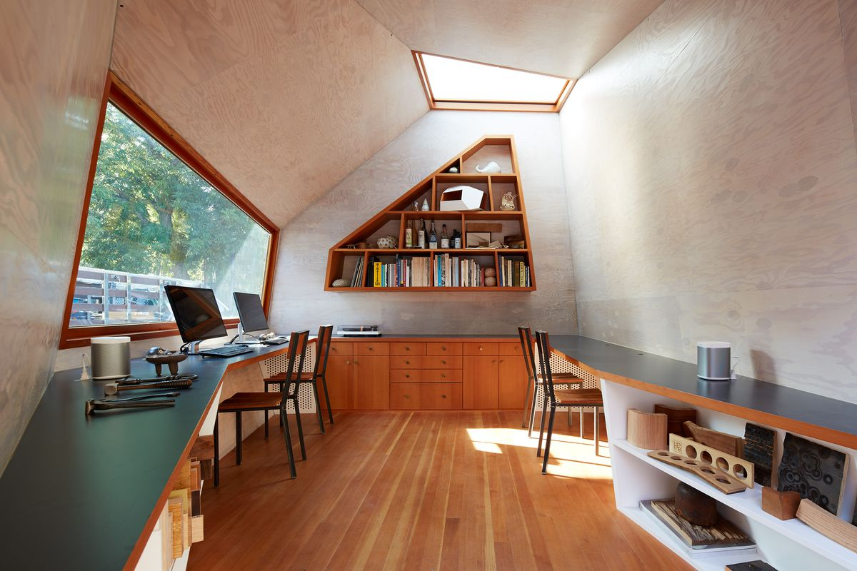 Wood interior with built-in desks and angular bookshelves