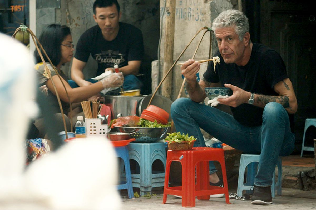 Anthony Bourdain sitting on a stool in a street, eating a bowl of noodles with chopsticks