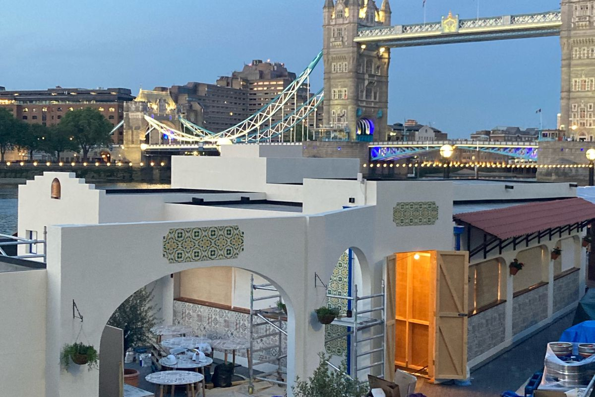 A Greek-style taverna pop-up mid-build by the River Thames, with Tower Bridge in the background
