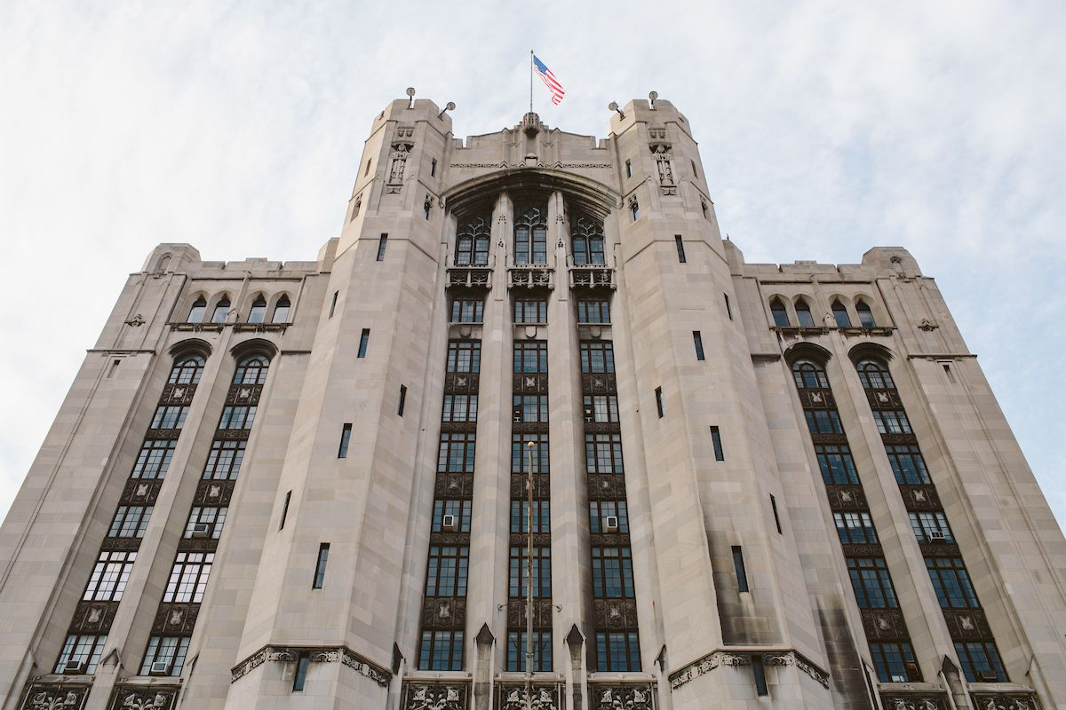 The exterior of the Masonic Temple in Detroit. The facade is tan and there are multiple windows. There is a flagpole on top of the building with a United States flag.