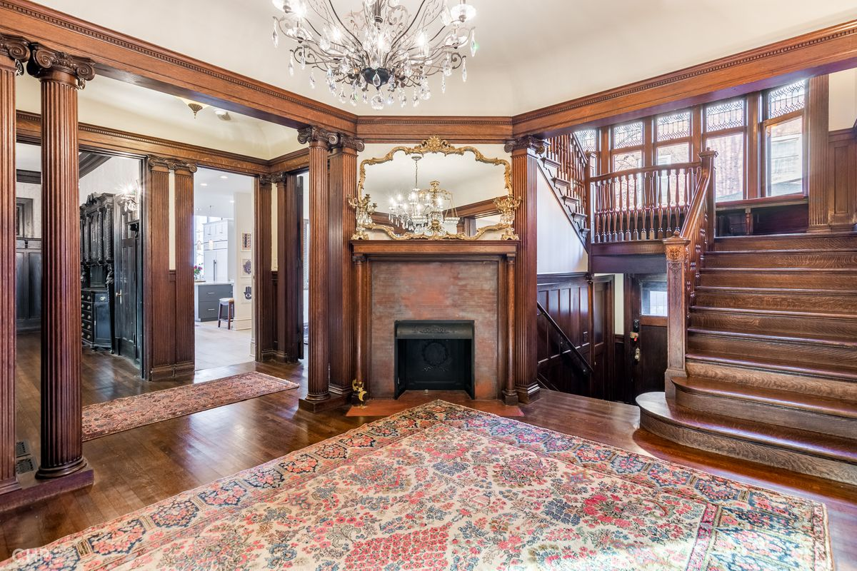 Wood stairs travel upwards next to a brick fireplace in a foyer. There are hardwood floors and carved columns leading to a dining room.