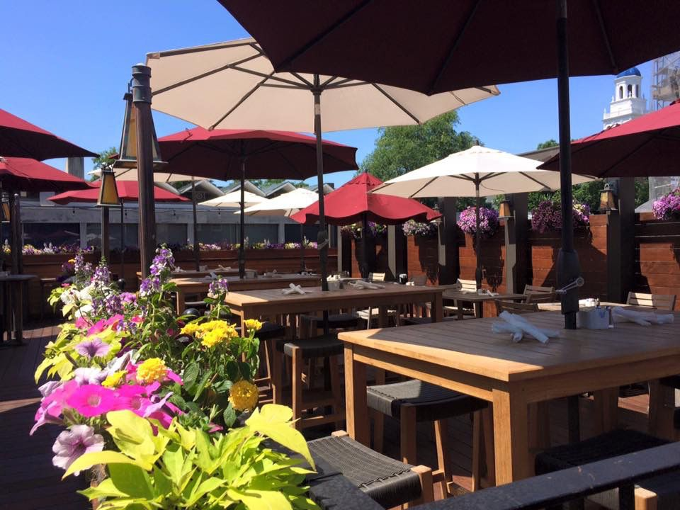 A restaurant's outdoor dining area features large wooden tables and a variety of umbrellas, some red and some white. Flowers are blooming in the foreground of the image.
