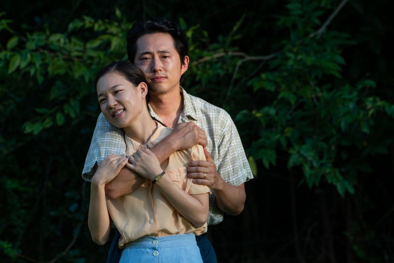 A Korean man and a woman stand in an embrace.