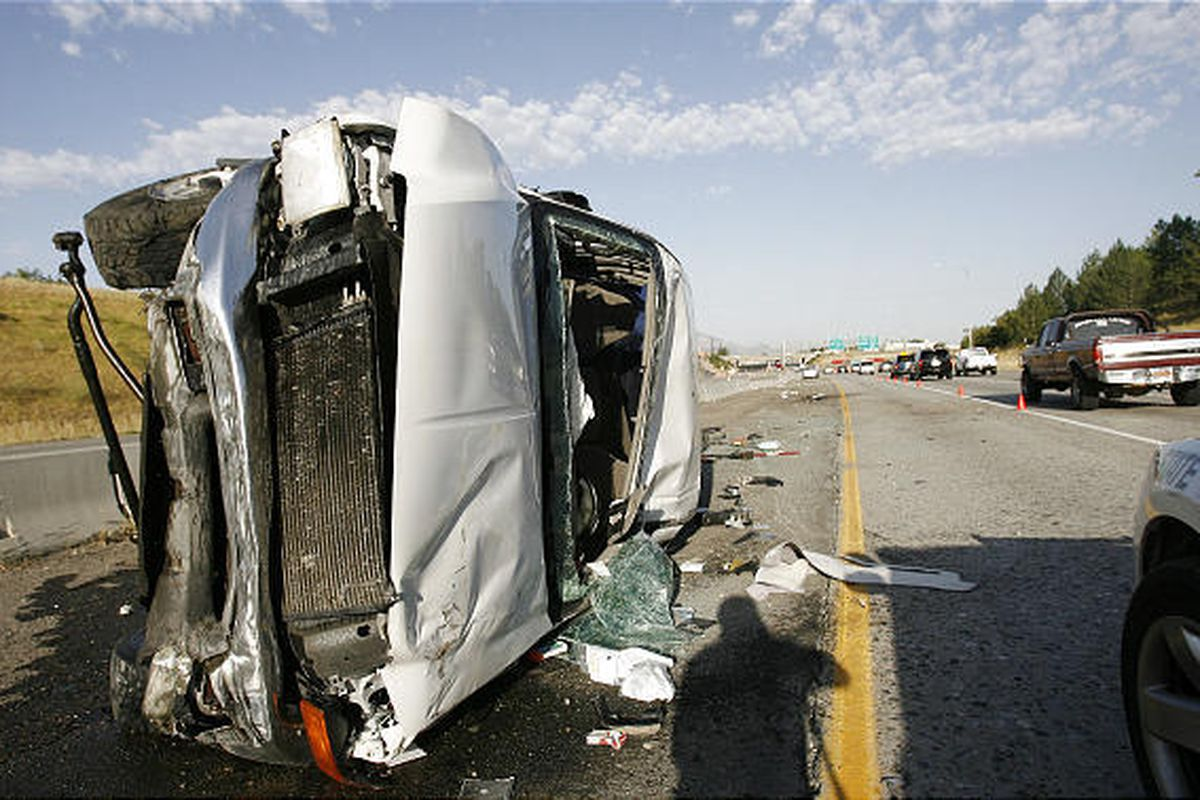 Law enforcers investigate the scene of a rollover on I-80 near 1700 East in Salt Lake City on Friday morning.