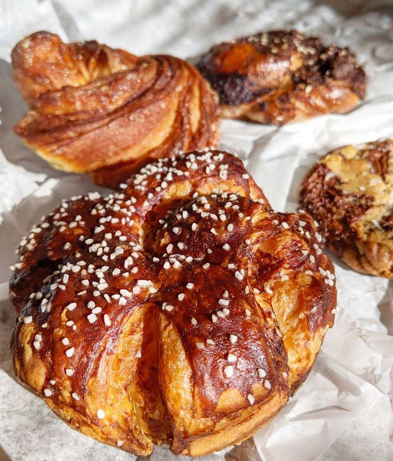A pretzel-croissant hybrid and several other baked goods sit on white bakery paper