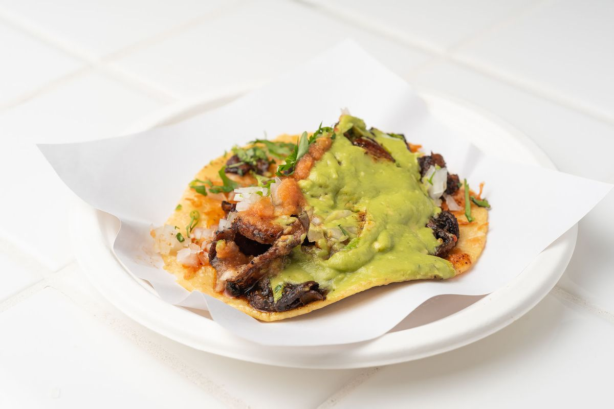 A corn tortilla taco on a white plate with guacamole sauce.