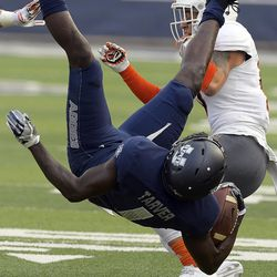 Utah State wide receiver Ron'quavion Tarver (1) is upended by Idaho State defensive back Tucker Louie-McGee during an NCAA football game Thursday, Sept. 7, 2017, in Logan, Utah. (Eli Lucero/Herald Journal via AP)
