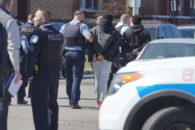 Police put a man in custody after a West Side shooting left an officer wounded Saturday.