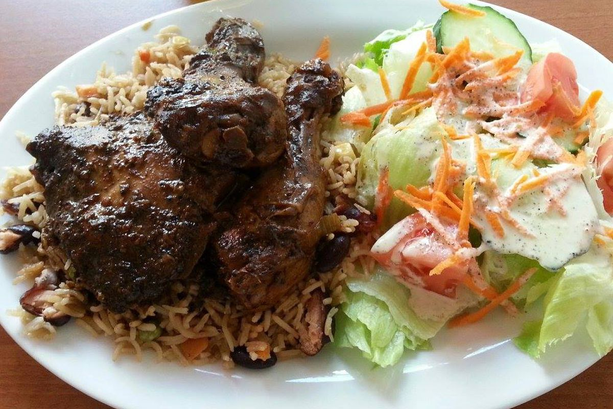 plate of jerk chicken, rice, and salad