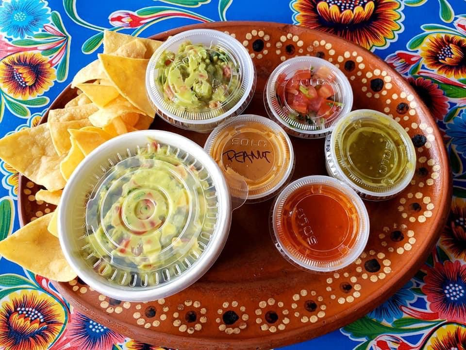 Chips with sides of guacamole and salsa.