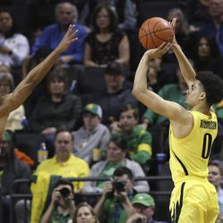 Oregon's Will Richardson, right, shoots over Utah's Alfonso Plummer during the second half of an NCAA college basketball game in Eugene, Ore., Sunday, Feb. 16, 2020.