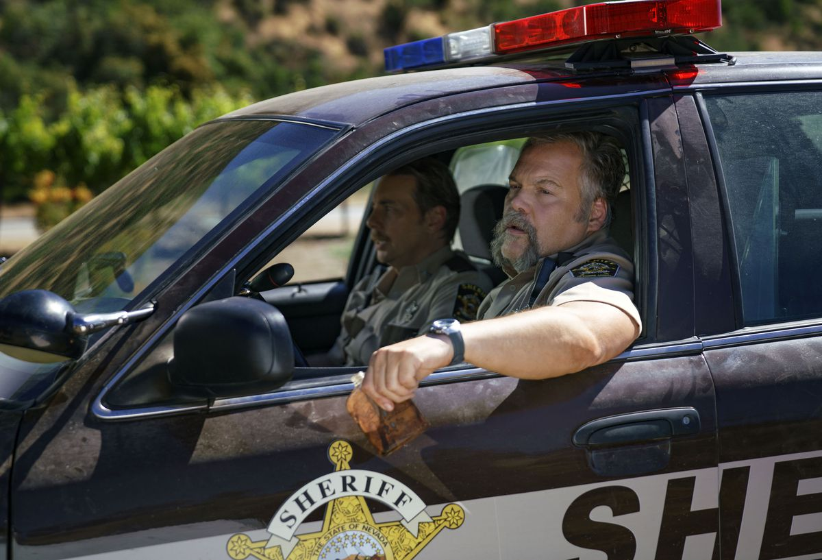 Vincent D'Onofrio and Dax Shepard in a police car.
