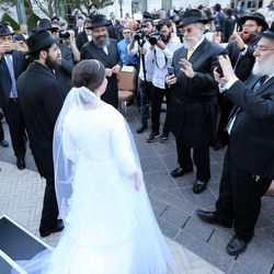 Rabbi Mendy Cohen and Chaya Zippel walk as husband and wife after their traditional Chabad Lubavitch Jewish wedding at the Grand America Hotel in Salt Lake City on Monday, Sept. 12, 2016.