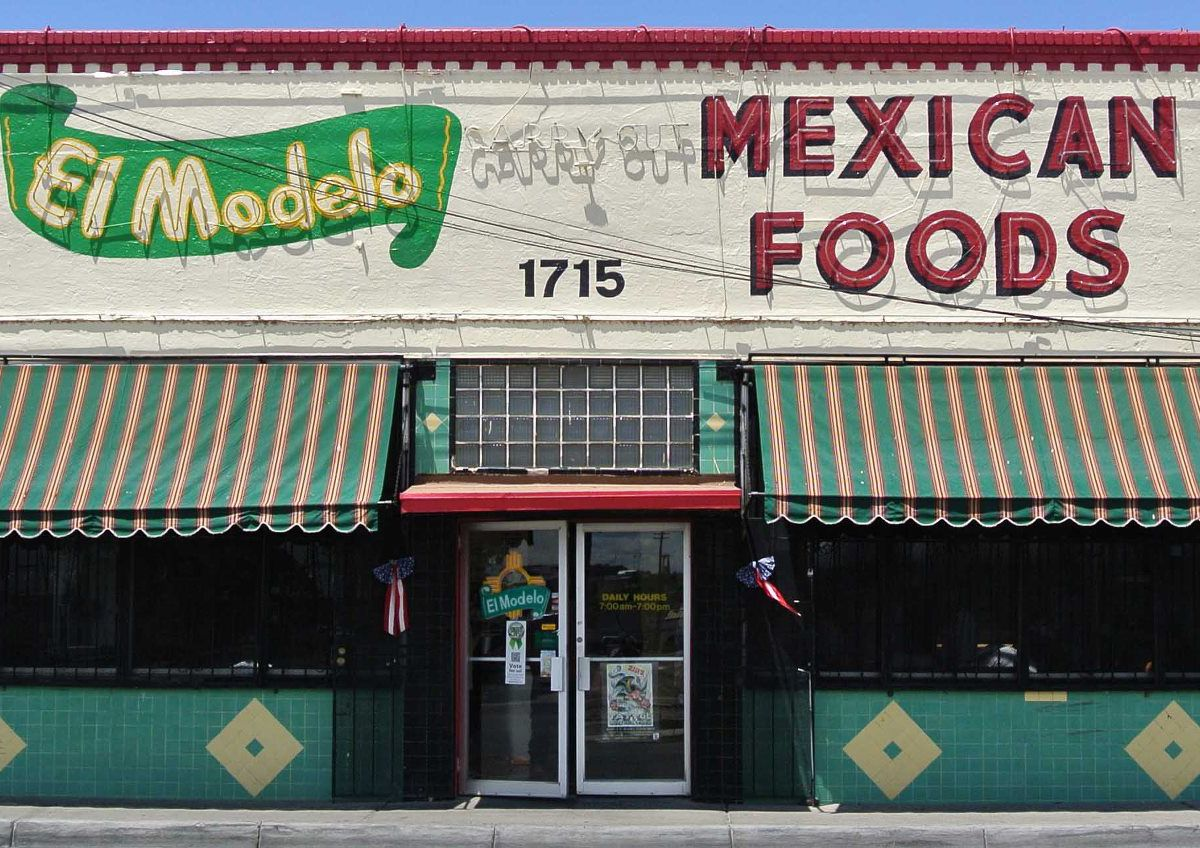 A storefront with bold graphic lettering, striped awnings, and festive faded paint