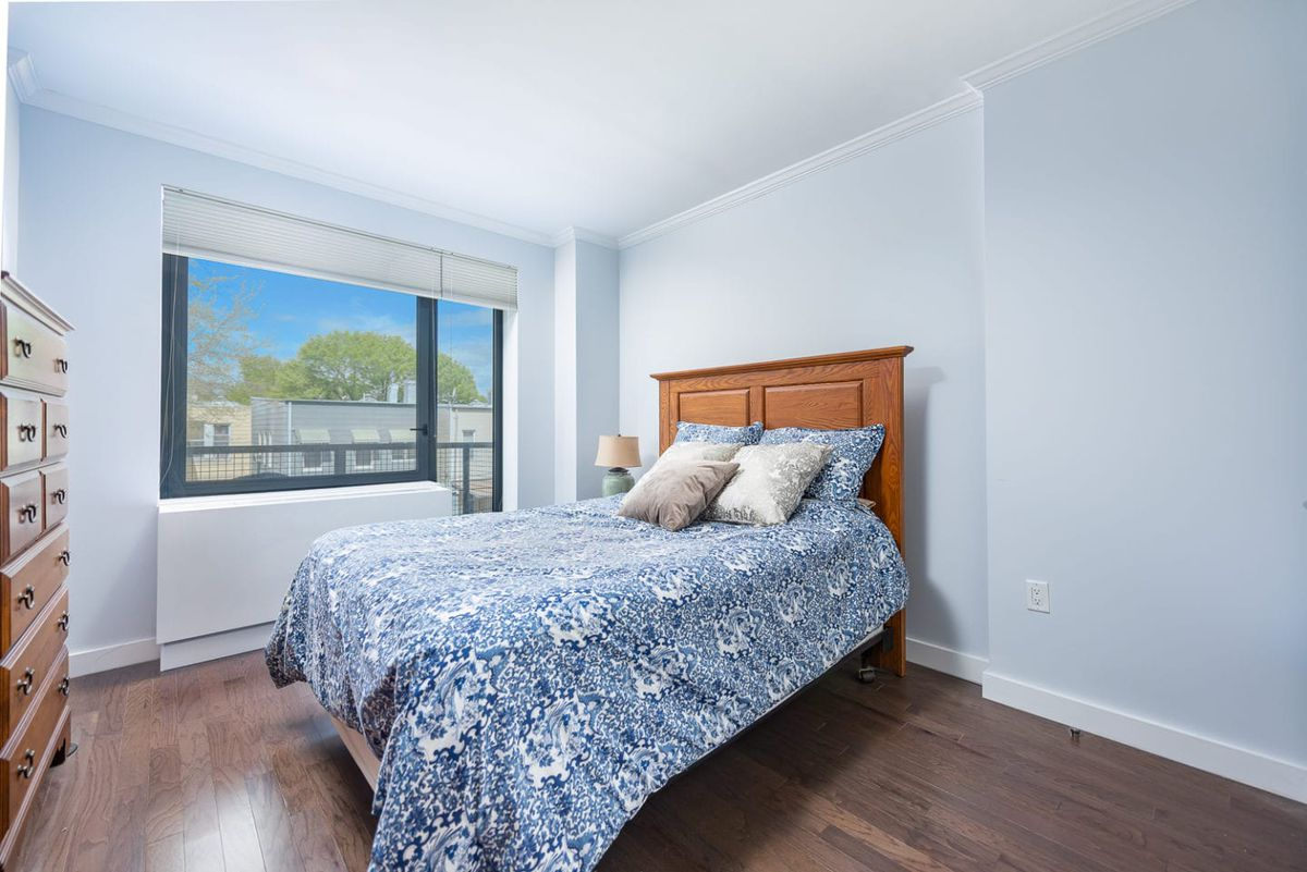 A bedroom with light blue walls, a large window that leads to a balcony, and a small bed.