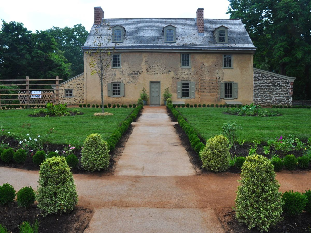 The exterior of a stone house in Philadelphia. There is a path with grass and shrubs on both sides in front of the house. The house has a grey roof.