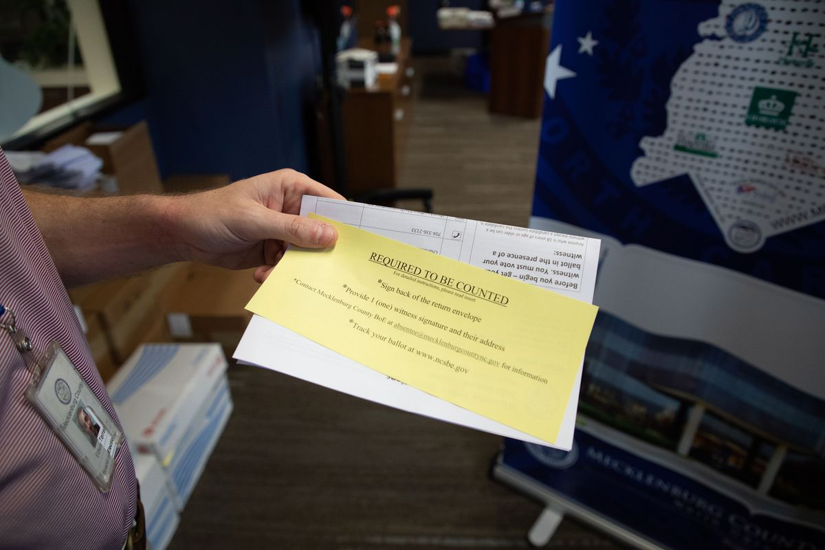 "Man holds up a yellow piece of paper that reads ""Required to be counted."""