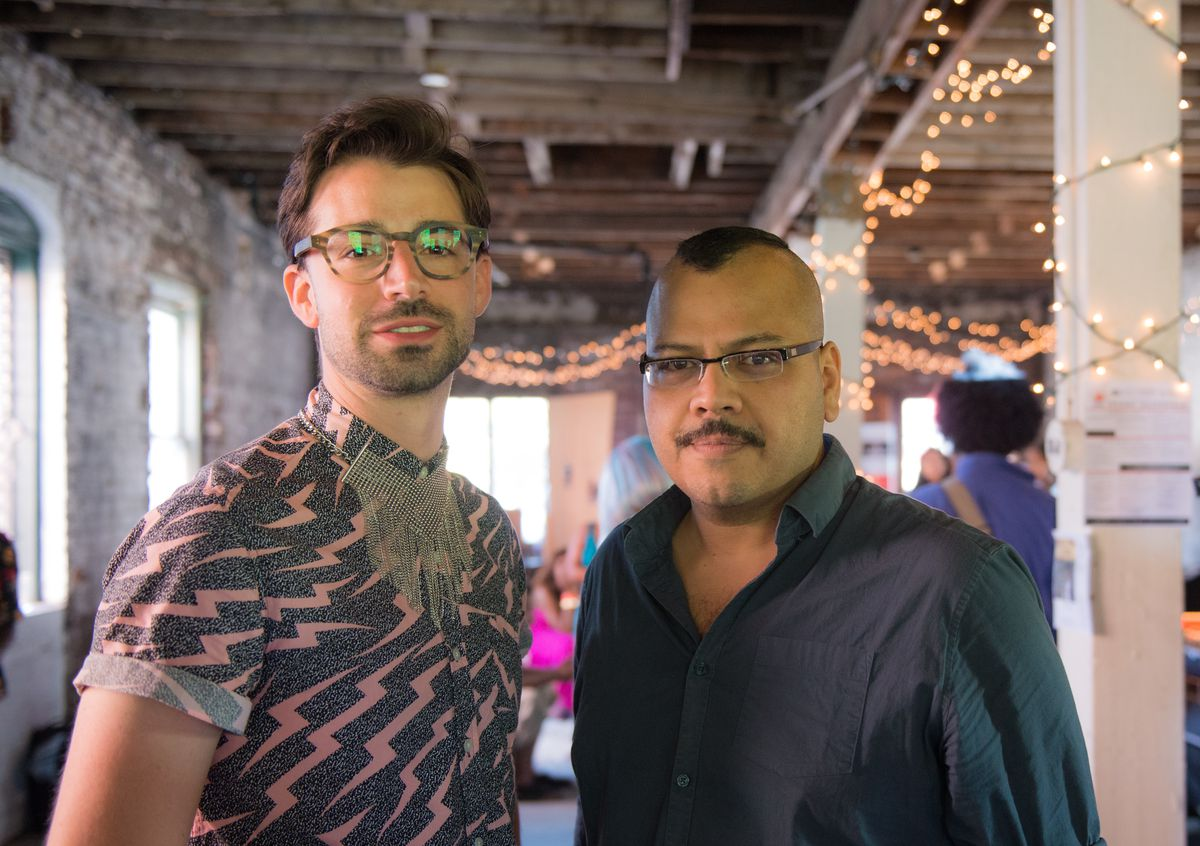 Two younger guys stand in a room with dangling lights.