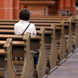 In this photo taken on Thursday, Sept. 27, 2012, a woman sits on a bench in the cathedral of Frankfurt, Germany.
