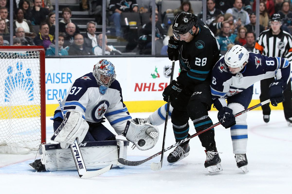 Dec 20, 2018; San Jose, CA, USA; Winnipeg Jets goaltender Connor Hellebuyck (37) attempts to grab the puck while San Jose Sharks right wing Timo Meier (28) looks for a rebound in front of Winnipeg Jets defenseman Jacob Trouba (8) during the second period