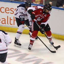 UConn's Max Letunov (27) battles with  Northeastern's John Stevens (18) for a loose puck.