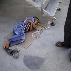 Syrian boy, Ali Fareed, 8, who fled his home with his family due to fighting between the Syrian army and the rebels, lies on the ground waiting for a doctor's arrival to check on him as he suffers from food poisoning, outside a makeshift clinic, at the Bab Al-Salameh border crossing where he and his family take refugee in hopes of entering one of the refugee camps in Turkey, near the Syrian town of Azaz, Friday, Sept. 7, 2012.